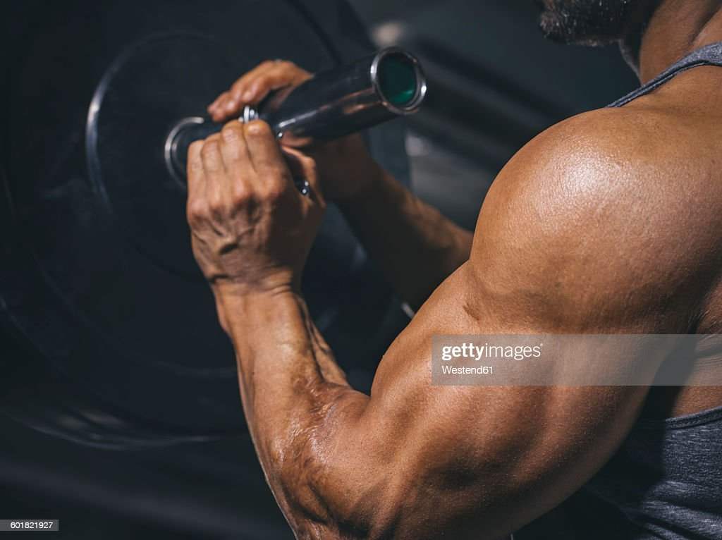 Bodybuilder preparing a barbell on a power rack in gym : Stock Photo