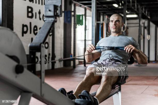Bodybuilder rowing hard in gym