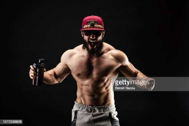 bodybuilder shouting, a protein shaker in his hand - body building stock pictures, royalty-free photos & images
