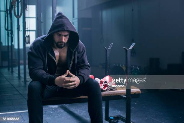 Bodybuilder wearing hoodie in a gym