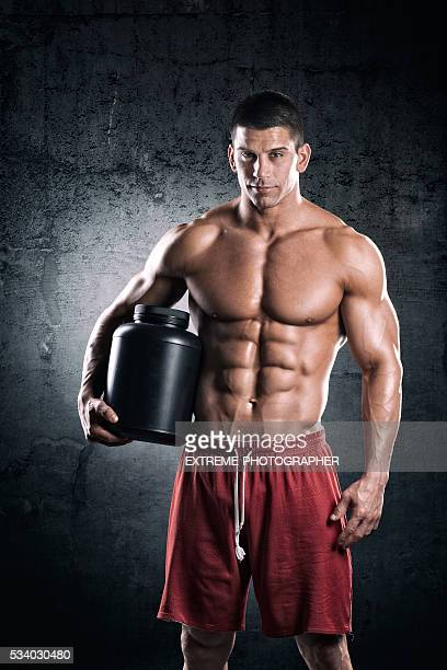 Bodybuilder with can of supplements