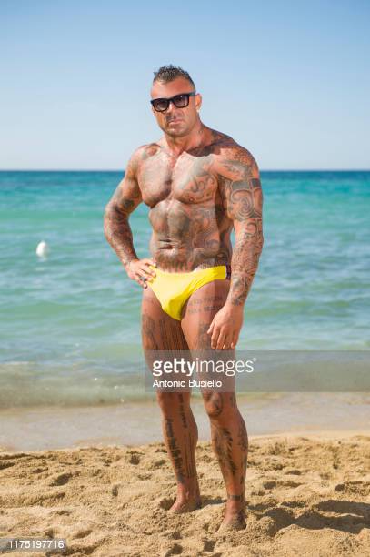 bodybuilder with tattoo wearing speedo - handsome bodybuilders stock pictures, royalty-free photos & images