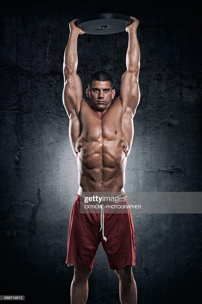 Bodybuilder con piastra di peso : Foto stock