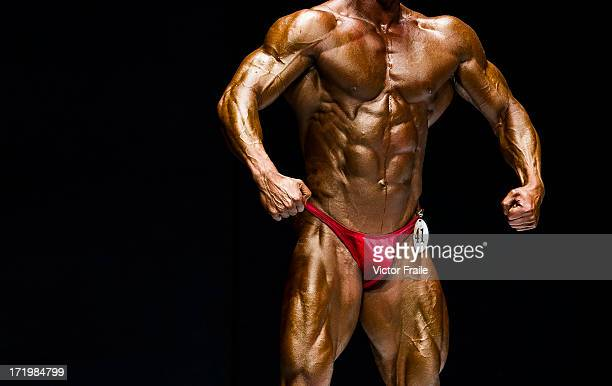 Bodybuilders flex their muscles for the judges on stage at the Hong Kong Bodybuilding Championships at the Queen Elizabeth Stadium Arena on June 30...