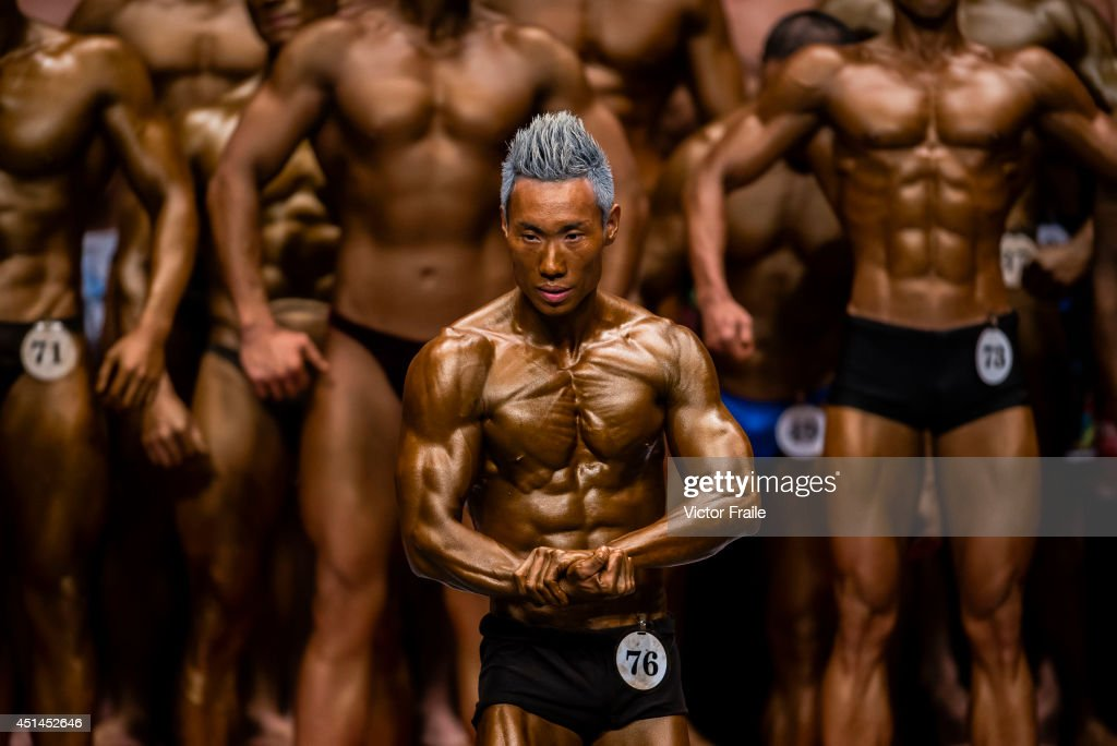 Bodybuilders flexe muscles for judges on stage during the Hong Kong Bodybuilding Championship on June 29, 2014 at the Queen Elizabeth Stadium in Hong Kong, Hong Kong.