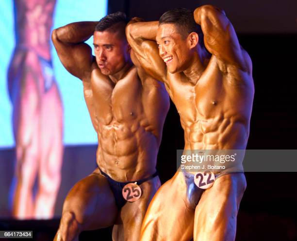 Bodybuilders pose on stage during the Fit Angel Classic at Queen Sirikit National Convention Center in Bangkok
