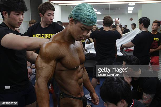 Bodybuilders prepare for judging backstage during the NABBA WFF Korea Championship on May 10 2015 in Seoul South Korea