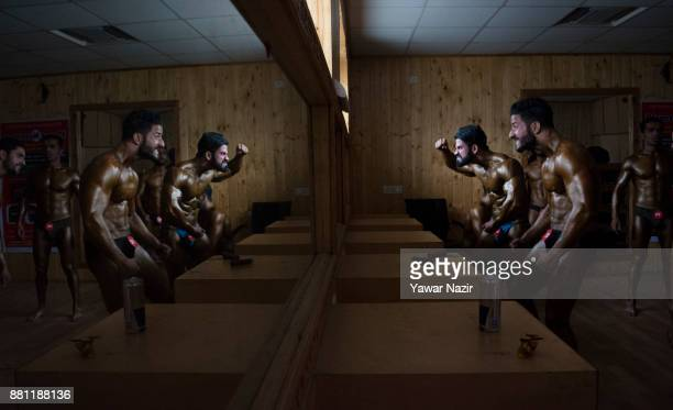 Bodybuilders warm up backstage before participating in the Mr Jammu and Kashmir Classic Bodybuilding Competition organized by Jammu and Kashmir...