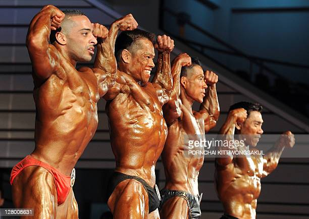 Bodybuilding contestants flex their muscles on stage during the first round of the Asian men's bodybuilding 55kg category at the Asian and World...