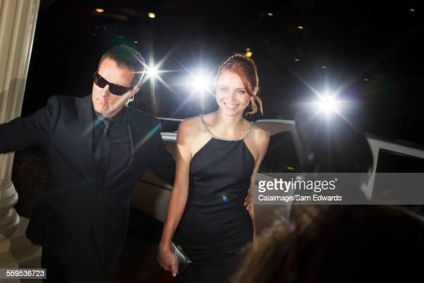 Bodyguard escorting smiling celebrity arriving at event