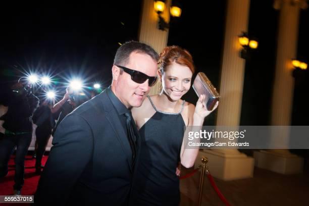 Bodyguard escorting smiling celebrity arriving at red carpet event