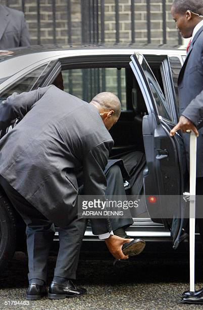 A bodyguard helps lift the foot of former South African President Nelson Mandela into his car after visiting British Prime Minister Tony Blair at...