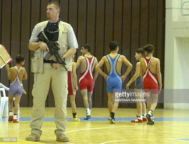 A bodyguard of Paul Bremer US top civil administrator in Iraq secures Baghdad's indoor Olympic Hall as Iraqi wrestlers train in the background 05...