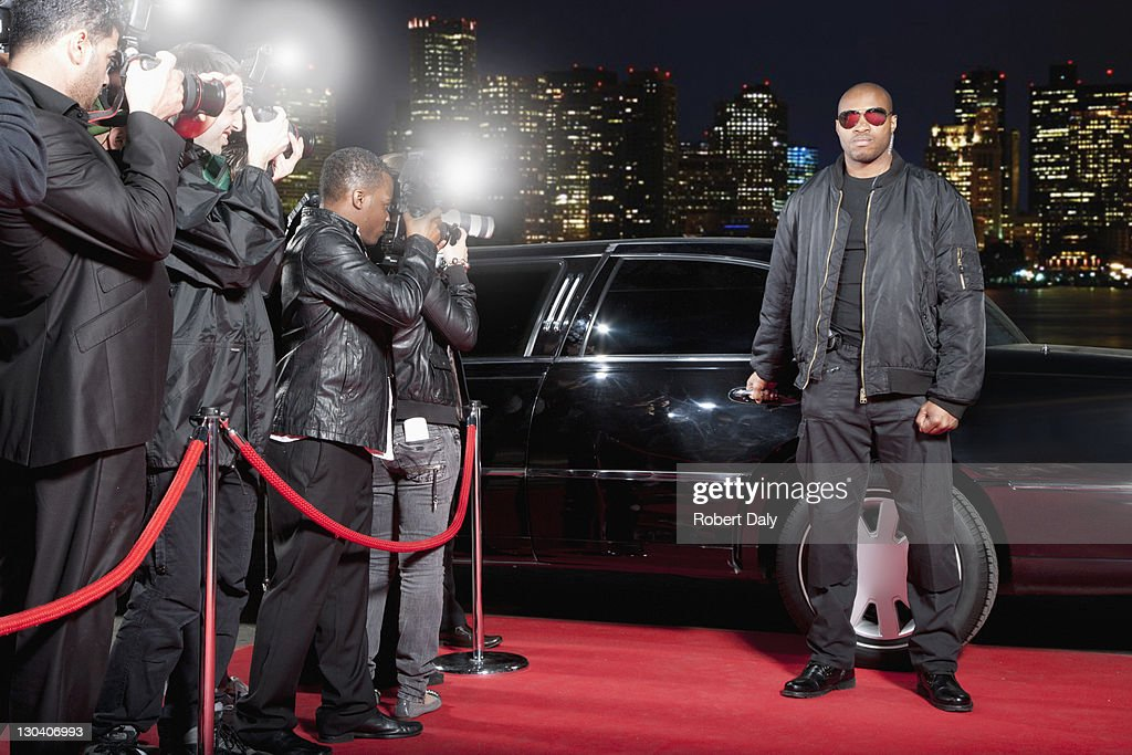 Bodyguard opening limo door on red carpet : Stock Photo
