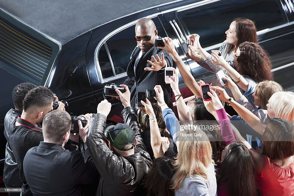 Bodyguard protecting celebrity from paparazzi : Stock Photo