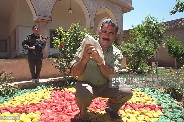 A bodyguard protects the PKK leader squatting on a replica of the PKK emblem