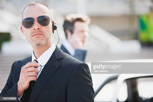bodyguard talking into earpiece - bodyguard stock pictures, royalty-free photos & images