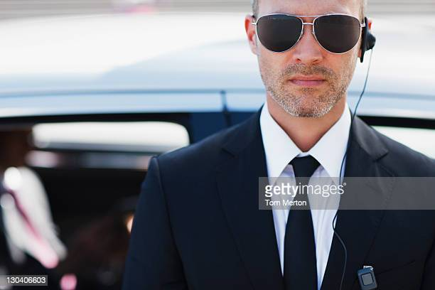 bodyguard wearing earpiece - protection stock pictures, royalty-free photos & images
