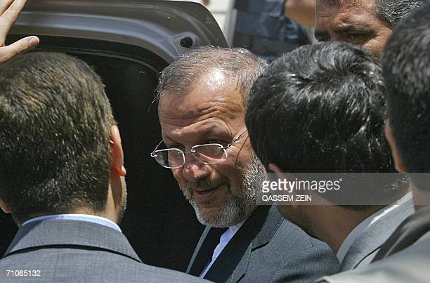 Bodyguards escort Iranian Foreign Minister Manouchehr Mottaki to his car after his meeting with Grand Ayatollah Ali al-Sistani in the holy city of...