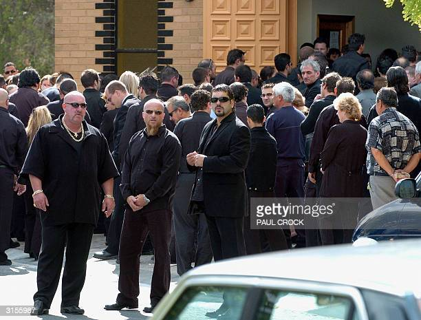 Bodyguards keep watch as mourners enter the church for the funeral of Andrew 'Benji' Veniamin, the 22nd victim of recent gangland murders, at the...