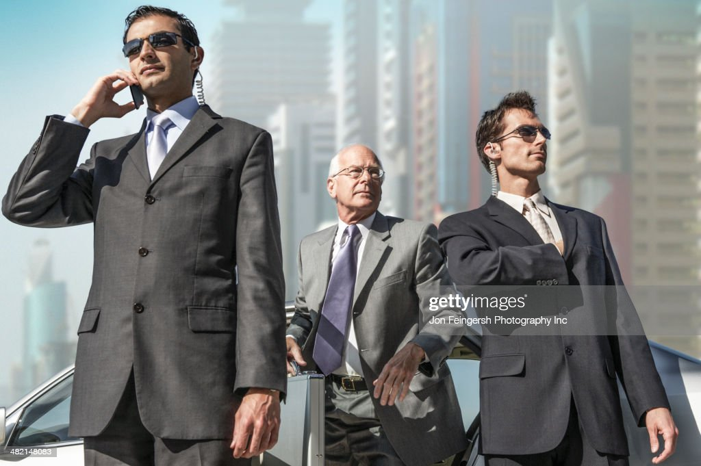 Bodyguards protecting businessman on city street : Stock Photo