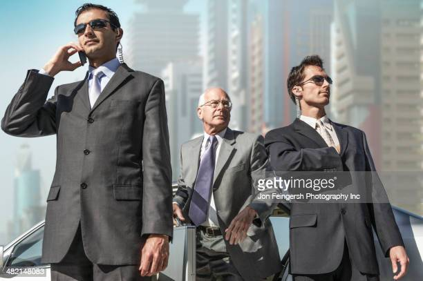 bodyguards protecting businessman on city street - guarding stock photos and pictures