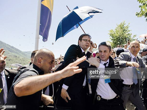 Bodyguards try to protect Serbian Prime Minister Aleksandar Vucic from stones hurled at him by an angry crowd at the Potocari Memorial Center near...