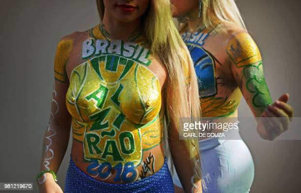 Bodypainted fans gather to watch a FIFA World Cup Russia 2018 football match between Brazil and Costa Rica on a giant screen at Alzirao neighborhood...