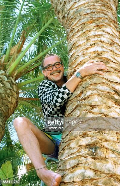 Boehm Werner * Entertainer Saenger D erklimmt eine Palme auf Gran Canaria Spanien in Montur seiner Figur 'Gottlieb Wendehals'