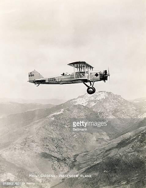 A Boeing 40A express mail plane flies over an expanse of mountains in the late 1920s