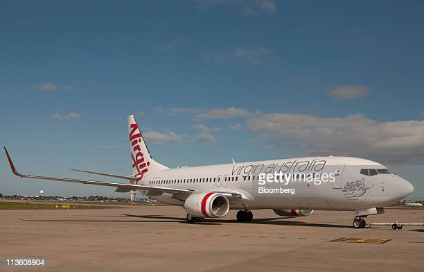 A Boeing 737 passenger jet bearing the new livery of Virgin Australia Airlines Pty Ltd touches down for its unveiling as the new face of the Virgin...