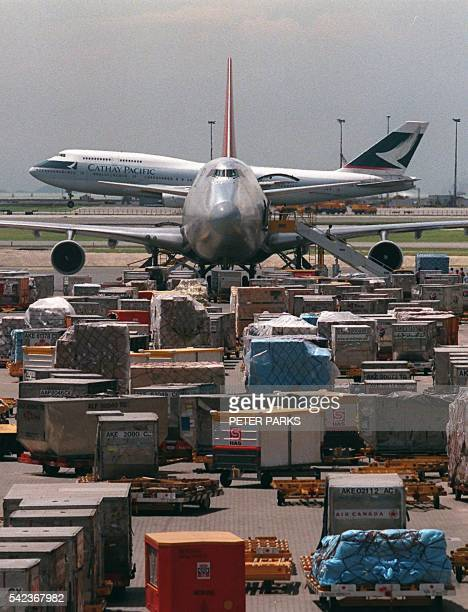 A Boeing 747 cargo plane sits whilst a passenger plane lands behind at Hong Kong International Airport at Chek Lap Kok 08 July with tonnes of cargo...