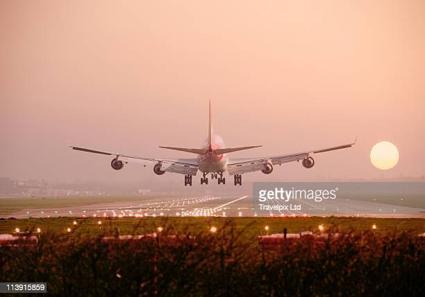 boeing 747 landing into sunset - landing gear stock photos and pictures