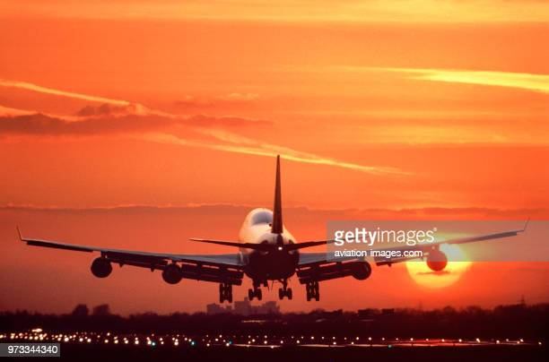 Boeing 747 landing on the runway at sunset with runwaylights on and Windsor Castle in the distance behind