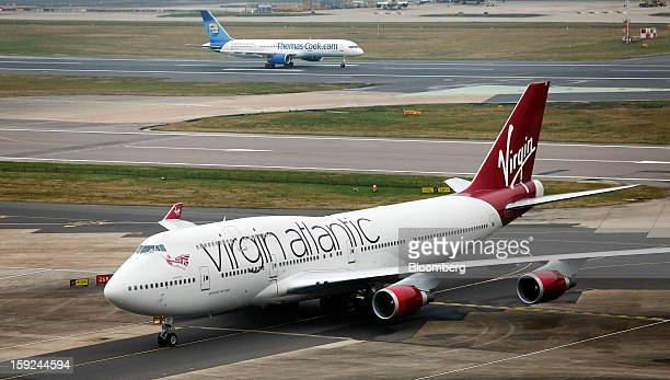 A Boeing 747400 aircraft operated by Virgin Atlantic left taxis as a Thomas Cook Group Plc aircraft prepares to take off at Gatwick airport in...