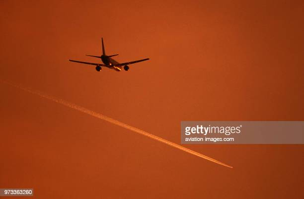 Boeing 757200 flying enroute with an airliner contrail above at dusk