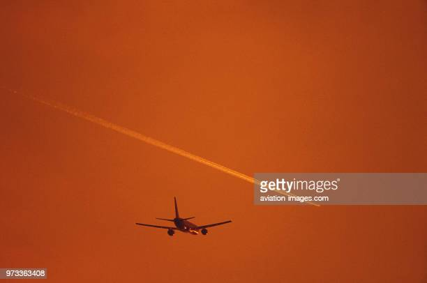 Boeing 757-200 flying enroute with an airliner contrail above at dusk.