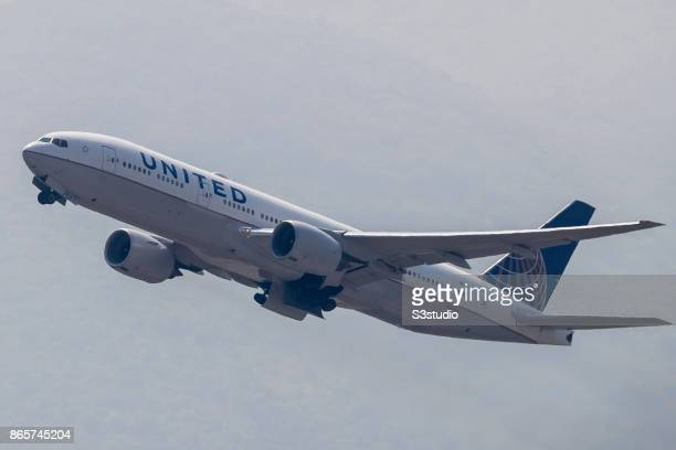 Boeing 777 passenger plane belonging to the United Airlines flies into the clouds after lifting off from Hong Kong International Airport on 23...