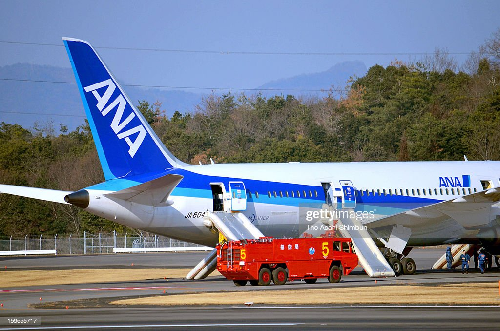 A Boeing 787 airplane is seen while firefighters are on stand-by at the runway of Takamatsu Airport on January 16, 2013 in Takamatsu, Kagawa, Japan. All Nippon Airways flight 692, departing from Yamaguchi Ube airport at 8:10 detected smoke inside the aircraft, made an emergency landing at Takamatsu Airport on 8:45, all 137 passengers and crews evacuated from the plane.
