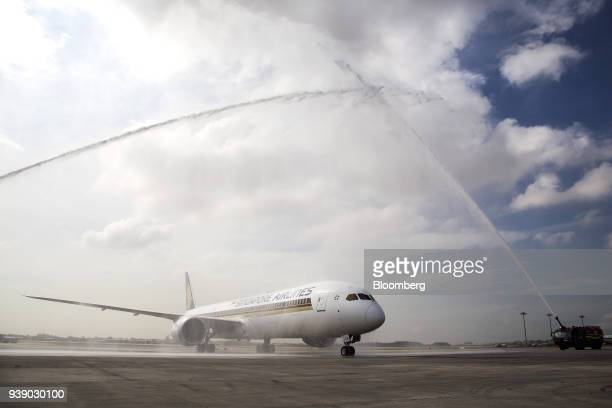 A Boeing 78710 Dreamliner aircraft operated by Singapore Airlines Ltd receives a water cannon salute as it arrives at Changi Airport in Singapore on...