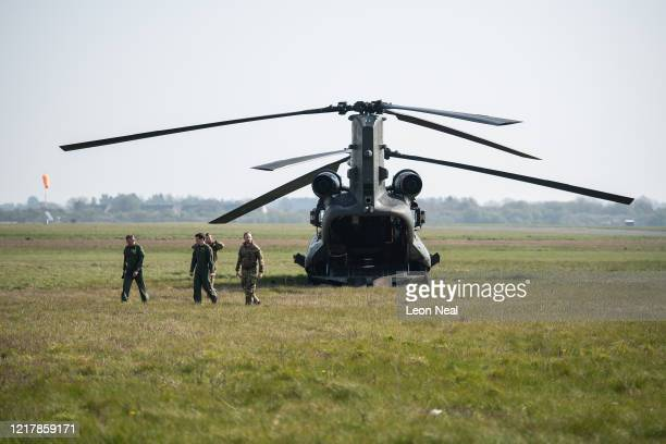 Boeing CH47 Chinook helicopter aircrew walk from their aircraft as members of the UK Armed Forces work with NHS medical staff and Air Ambulance...