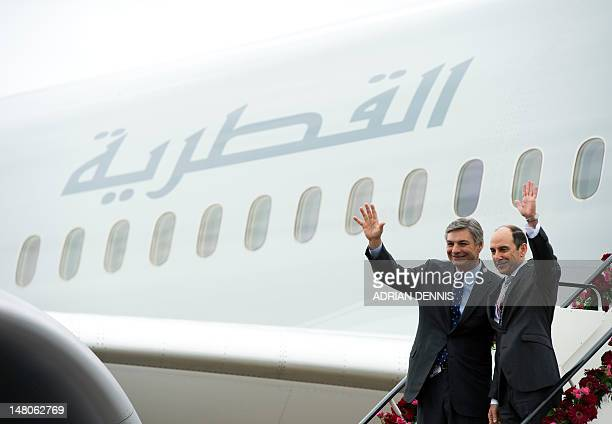 Boeing Chief Executive Ray Conner and Qatar Airways CEO Akbar Al Baker wave from the steps of the Boeing 787 Dreamliner at the Farnborough...