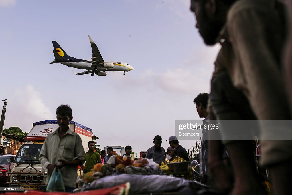 A Boeing Co. 737 aircraft operated by Jet Airways India Ltd. flies over a street market as it approaches to land at Chhatrapati Shivaji International Airport in Mumbai, India, on Saturday, June 27, 2015. Jet Airways is India's Second biggest airline by market share according to the Indian Aviation Ministry. Photographer: Dhiraj Singh/Bloomberg via Getty Images