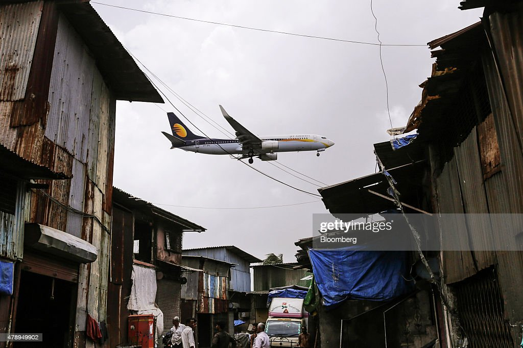 A Boeing Co. 737 aircraft operated by Jet Airways India Ltd. flies over slum housing as it approaches to land at Chhatrapati Shivaji International Airport in Mumbai, India, on Saturday, June 27, 2015. Jet Airways is India's Second biggest airline by market share according to the Indian Aviation Ministry. Photographer: Dhiraj Singh/Bloomberg via Getty Images