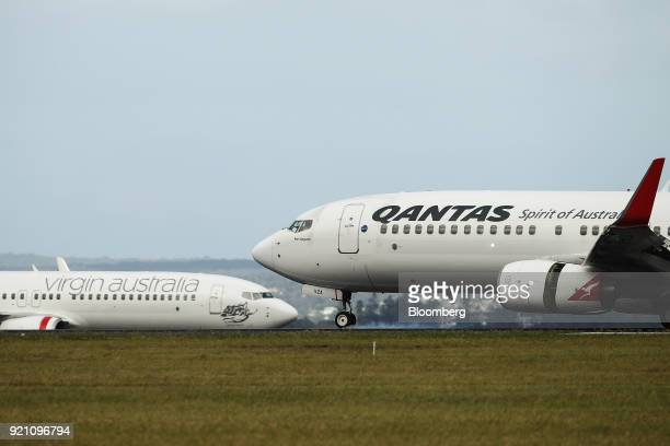 A Boeing Co 737800 aircraft operated by Qantas Airways Ltd right passes an aircraft operated by Virgin Australia Holdings Ltd on the tarmac at Sydney...