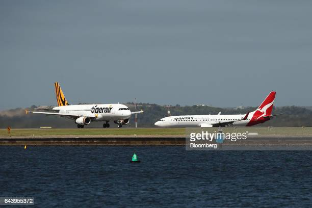 A Boeing Co 737800 aircraft operated by Qantas Airways Ltd right waits for an Airbus SE A320200 aircraft operated by Tiger Airways Holdings Ltd to...