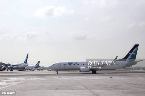 A Boeing Co 737800 aircraft operated by SilkAir Singapore Pte a unit of Singapore Airlines Ltd taxies along the tarmac at Changi Airport in Singapore...