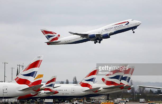 A Boeing Co 747 passenger aircraft operated by British Airways a unit of International Consolidated Airlines Group SA takes off over a row of...