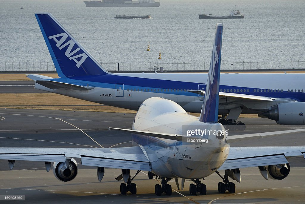 A Boeing Co. 747-400 aircraft, front, and a Boeing Co. 777-200 aircraft, both operated by All Nippon Airways Co. (ANA), line up on the runway prior to take off at Haneda Airport in Tokyo, Japan, on Wednesday, Jan. 30, 2013. ANA has canceled a total of 784 flights, affecting 74,200 passengers through Feb. 12, since a Jan. 16 incident that led to the global grounding of Boeing Co. 787s, according to figures from the company. Photographer: Akio Kon/Bloomberg via Getty Images