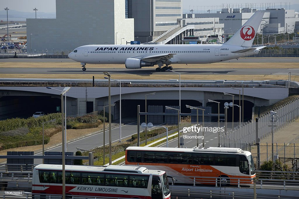 A Boeing Co. 777 aircraft operated by Japan Airlines Co. (JAL) taxis on the tarmac as traffic passes by on roads around Haneda Airport in Tokyo, Japan, on Sunday, Feb. 3, 2013. Japan Airlines, the nation's largest carrier by market value, is scheduled to release earnings on Feb. 4. Photographer: Akio Kon/Bloomberg via Getty Images